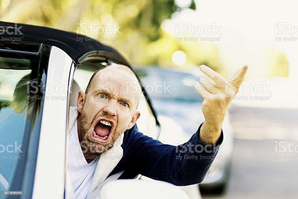 Enraged male driver shouts and gestures threateningly stock photo