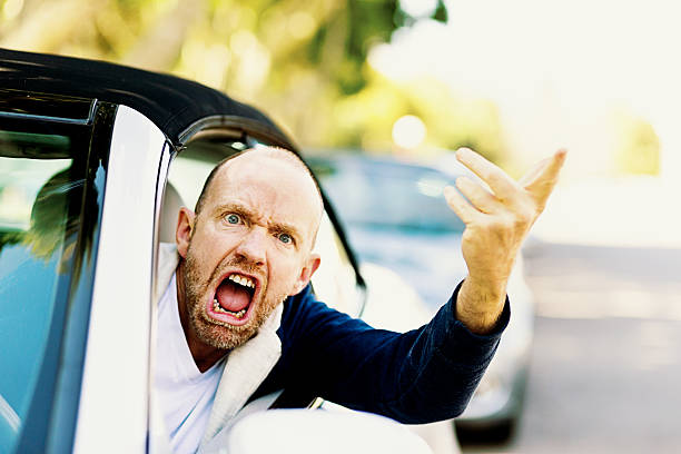 Enraged male driver shouts and gestures threateningly A furiously angry male driver grimaces, gesturing threateningly through the car window in a bout of road rage! aggression stock pictures, royalty-free photos & images