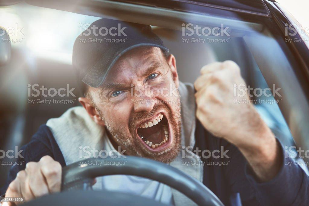 Enraged man shaking fist through windscreen: road rage stock photo