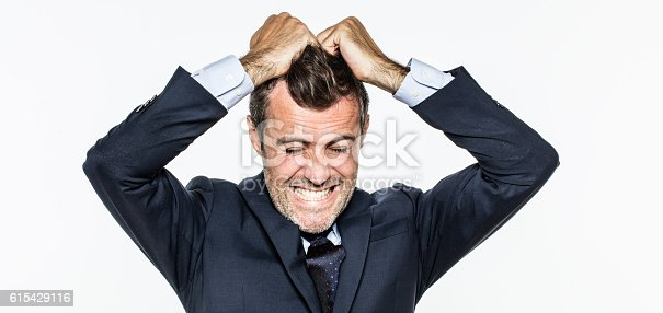 istock enraged young businessman pulling his hair out for exasperation 615429116