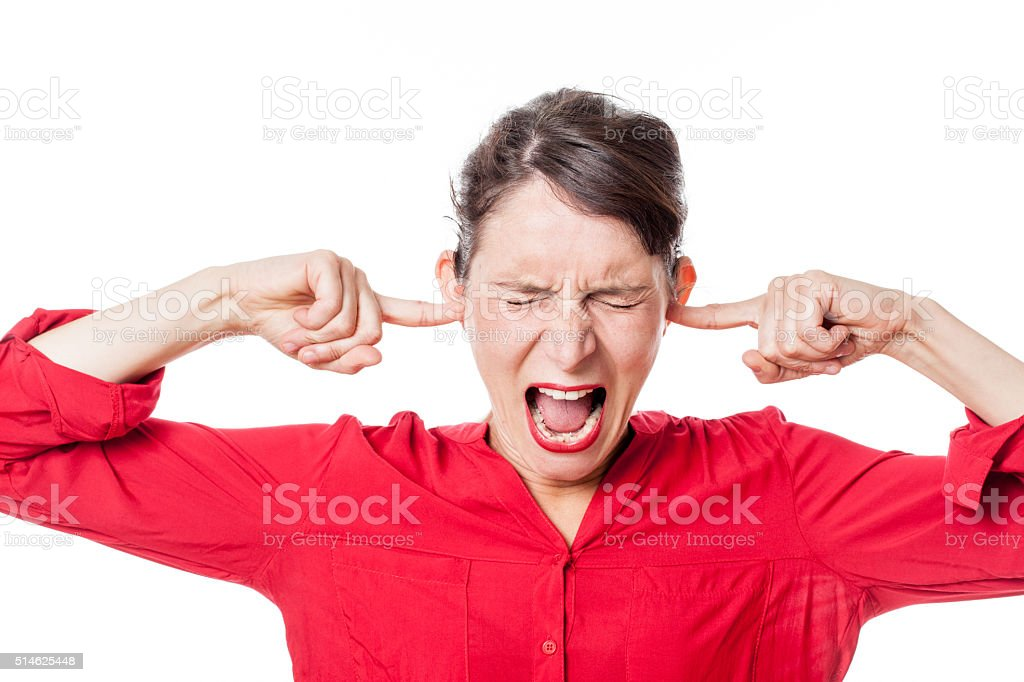 enraged young woman screaming, plugging her ears stock photo