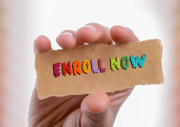 Enroll now wording written on blank torn paper in hand stock photo