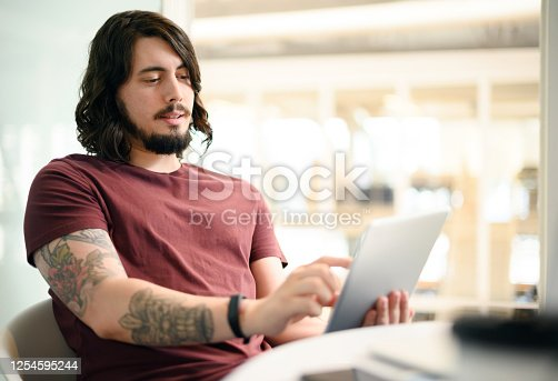Shot of a young businessman using a digital tablet in an office