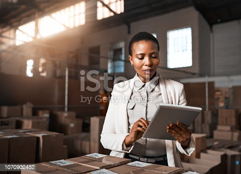 Shot of a factory manager using a digital tablet in a warehouse
