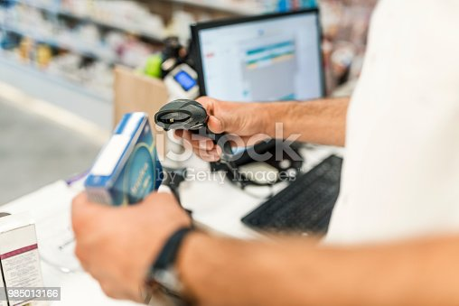 Photo of Caucasian  Unrecognizable male Pharmacist scanning price on a blue medicine box with bar-code reader in pharmacy drugstore.