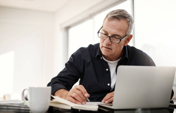 Ensuring his calculations stay spot on Shot of a mature man going through some paperwork at home only senior men stock pictures, royalty-free photos & images