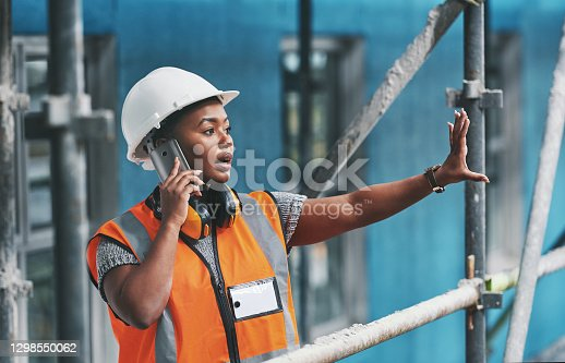 Shot of a young woman talking on a cellphone while working at a construction site
