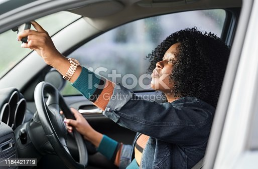 Shot of a mature african woman sitting in a car driving seat and adjusting rear view mirror