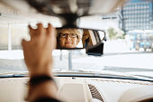 Portrait of a mature businesswoman looking in the rearview mirror of a car while driving