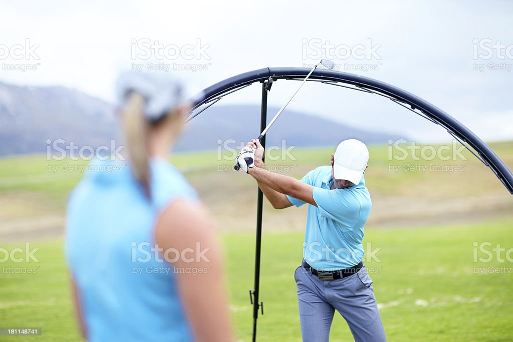 Ensuring she learns the perfect swing royalty-free stock photo