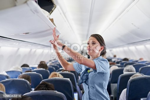 Shot of a young air hostess closing the overhead compartment on an airplane