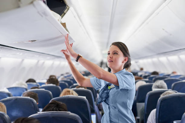 Ensuring your comfort and safety Shot of a young air hostess closing the overhead compartment on an airplane cabin crew stock pictures, royalty-free photos & images