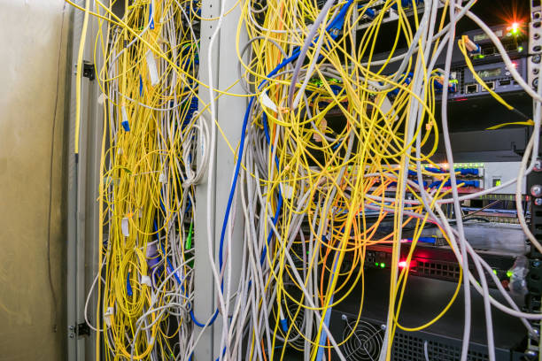 Entangled Internet wires are in the server room. Disorderly connection of optical cables with computer equipment. Racks with servers are located in the datacenter Entangled Internet wires are in the server room. Disorderly connection of optical cables with computer equipment. Racks with servers are located in the datacenter anode stock pictures, royalty-free photos & images