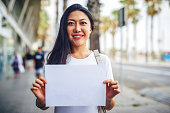 Cropped portrait of an attractive young woman standing on the street and holding up a poster while sight-seeing in Spain