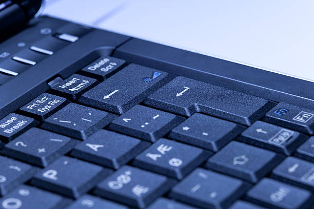 Enter key on laptop in blue tint stock photo