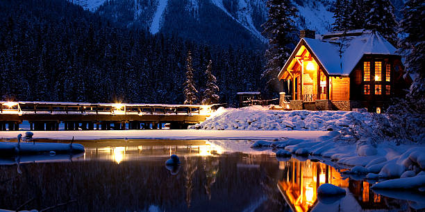 "Entering a Magical Winter Wonderland The bridge entering Emerald Lake Lodge and the Lodge's ""Cilantro"" Restaurant reflected in a wintery pond. emerald lake stock pictures, royalty-free photos & images"