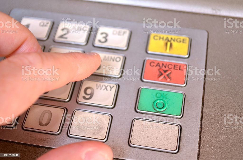 Entering a Secure pin into an ATM machine stock photo