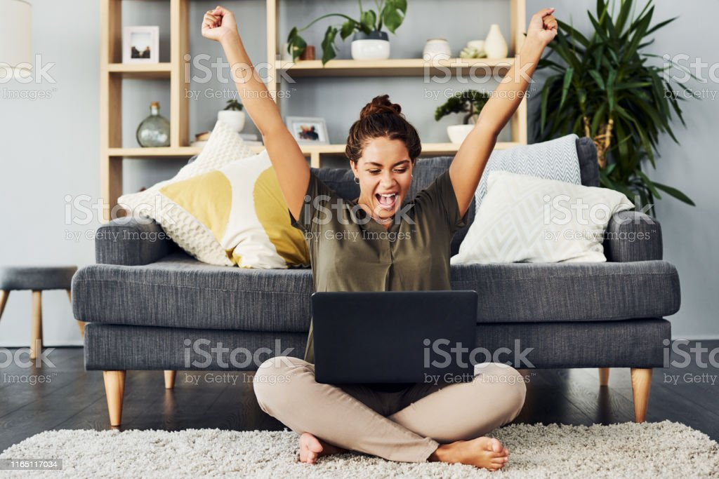 Entering all those competitions finally paid off Shot of a young woman cheering while using a laptop on the living room floor at home Achievement Stock Photo