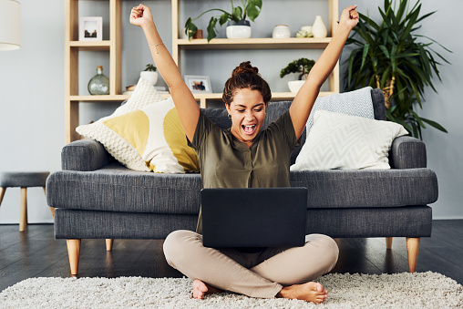 Shot of a young woman cheering while using a laptop on the living room floor at home