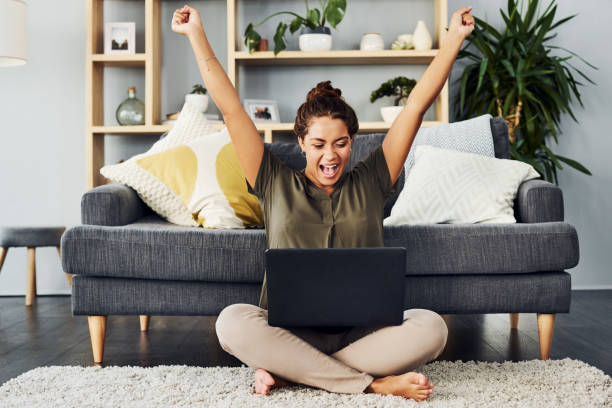 Entering all those competitions finally paid off Shot of a young woman cheering while using a laptop on the living room floor at home excited stock pictures, royalty-free photos & images