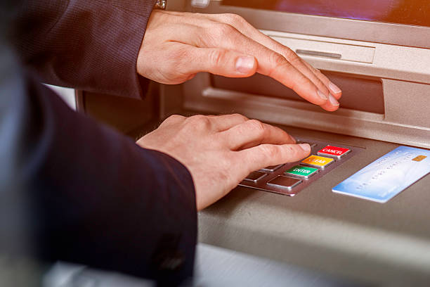 Entering ATM cash machine PIN code stock photo