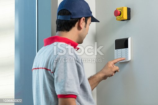 475693130 istock photo Entering code on keypad of security alarm 1036800322