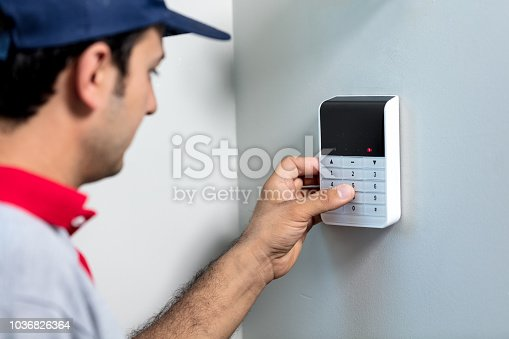 475693130 istock photo Entering code on keypad of security alarm 1036826364