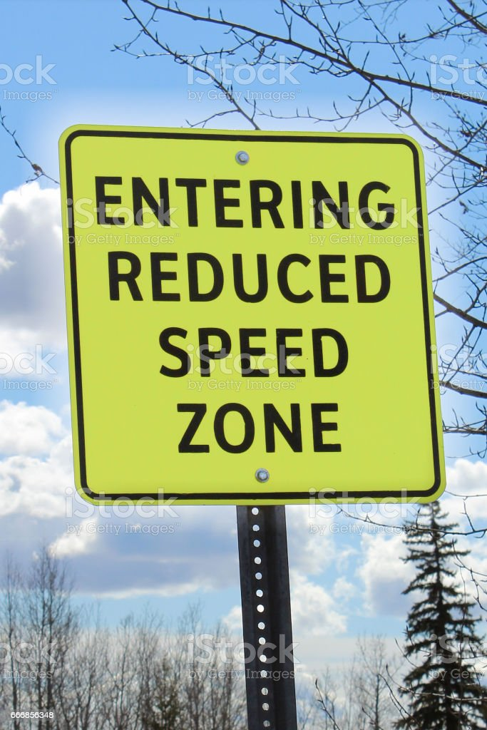 Entering reduced speed zone sign stock photo