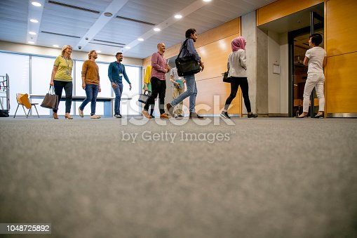 A multi-ethnic group of university staff and students enter a classroom, they are wearing smart casual clothing and blue lanyards.