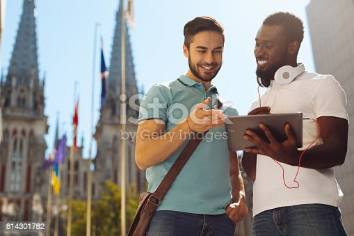 istock Enterprising remarkable guy showing his friend something 814301782