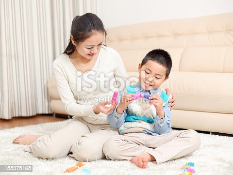 one boy is playing the plasticine with his mother