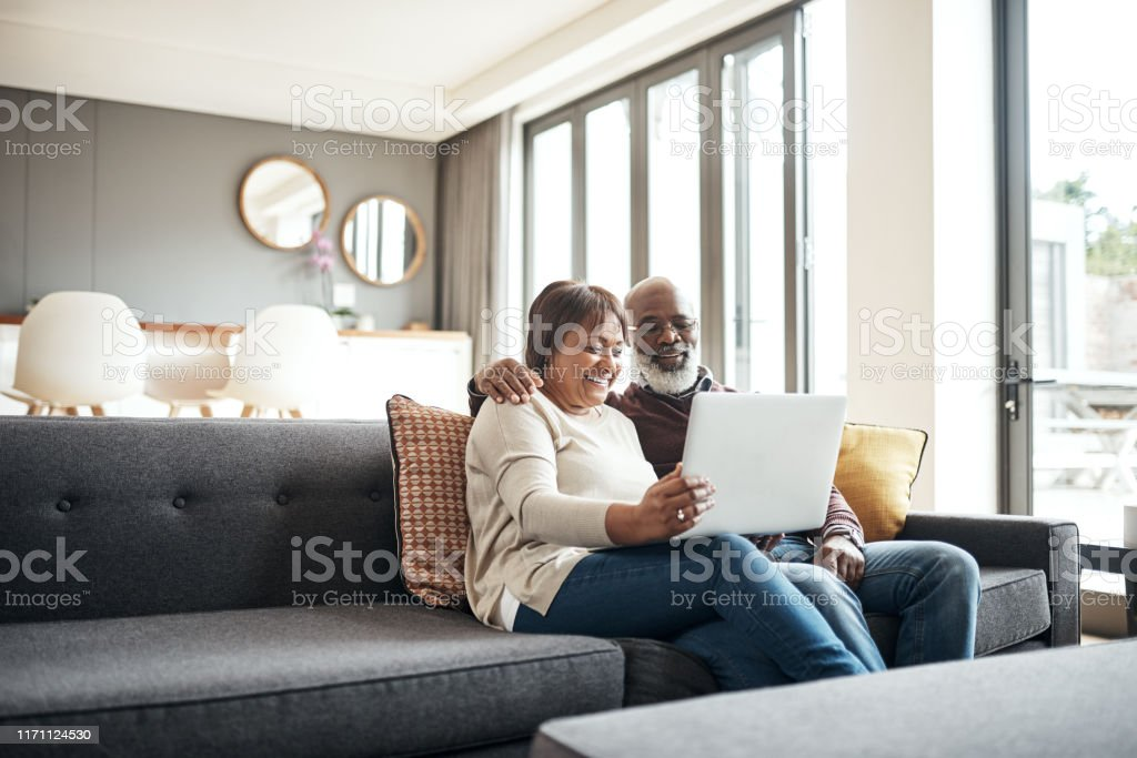 Entertained in the comfort of our own home Shot of a mature couple using a laptop while sitting together on the couch at home Active Seniors Stock Photo