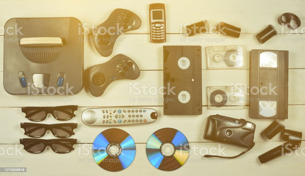 Entertainment 90s. Game console, gamepads, disks, audio cassettes, video cassettes, phone, film camera on a white wooden table. Top view. Flat lay. – zdjęcie