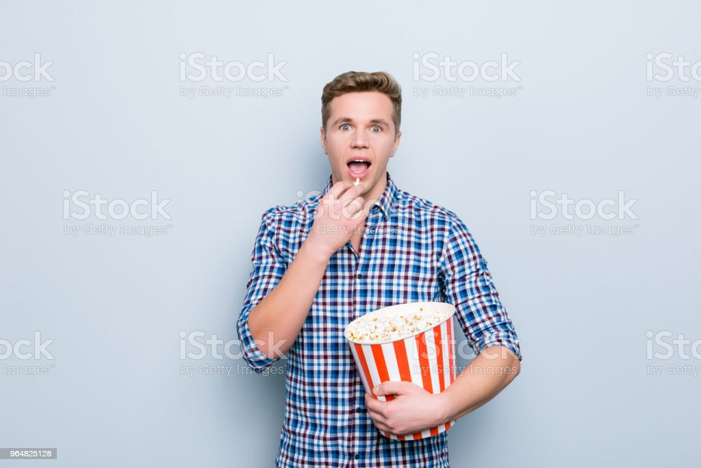 Entertainment camera look emotion expressing people person concept. Close up portrait of handsome astonished amazed glad excited pleased shocked student eating popcorn isolated on gray background royalty-free stock photo