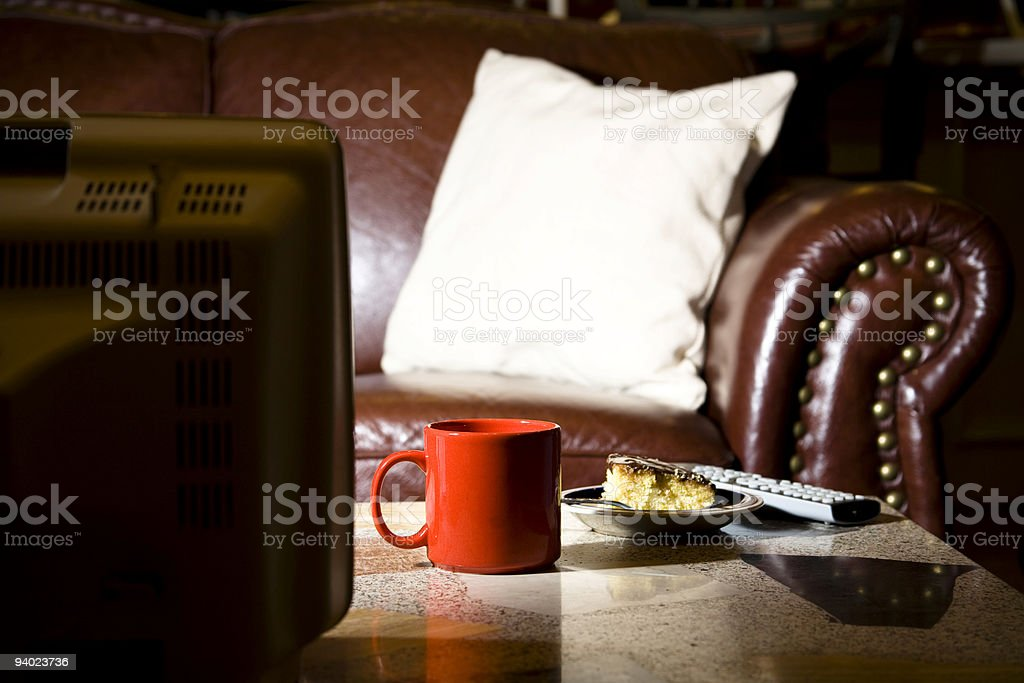 Entertainment: coffee and cake snack on table front of television royalty-free stock photo