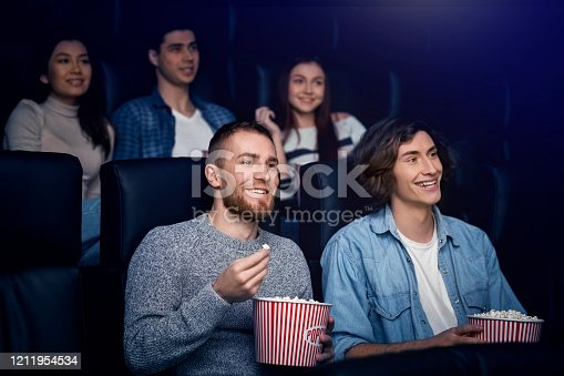 Entertainment concept. Happy young people with popcorn enjoying movie in cinema