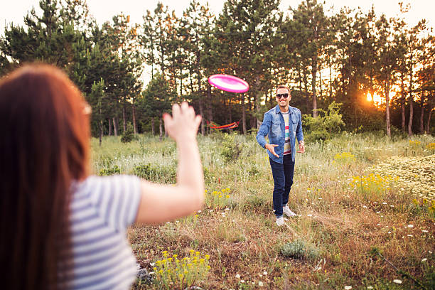 Entertainment Young couple is having fun throwing a frisbee in the park outdoors. plastic disc stock pictures, royalty-free photos & images