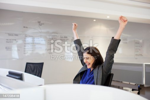 istock Enthusiastic businesswoman with arms raised in office 147205418