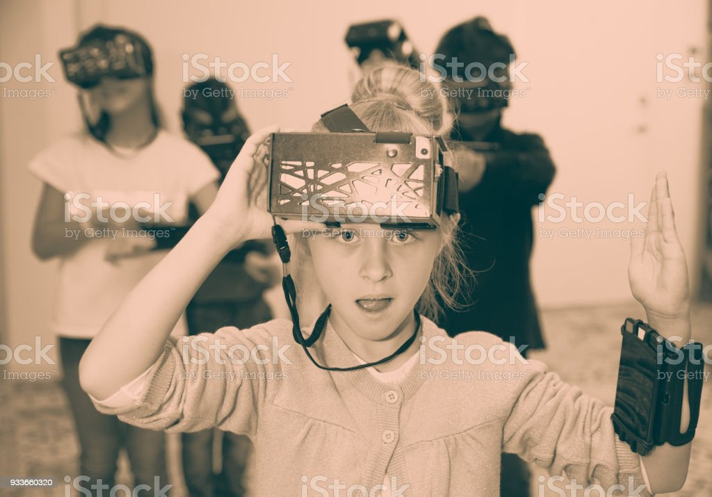 Enthusiastic children in virtual reality glasses in quest room stock photo
