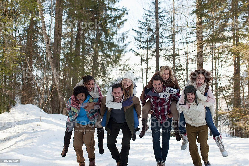 Enthusiastic couples piggybacking in snowy woods royalty-free stock photo
