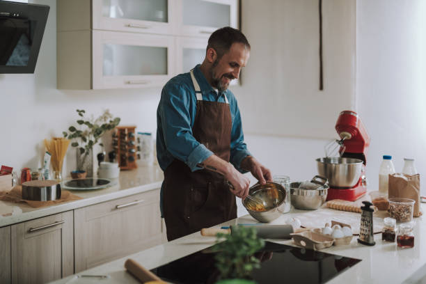 Enthusiastic man smiling while beating up eggs in bowl Cheerful emotional bearded man standing in the kitchen and smiling while holding a whisk and beating up eggs hobbies stock pictures, royalty-free photos & images