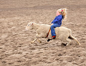 Little girl riding a sheep at a rodeo.  She seems totally happy and excited during the process.  With a big grin and big wide eyes she holds on tight so she doesn't fall off.