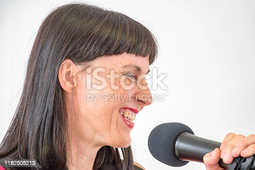 Enthusiastic Singer Woman Singing into  Microphone in the Recording Studio
