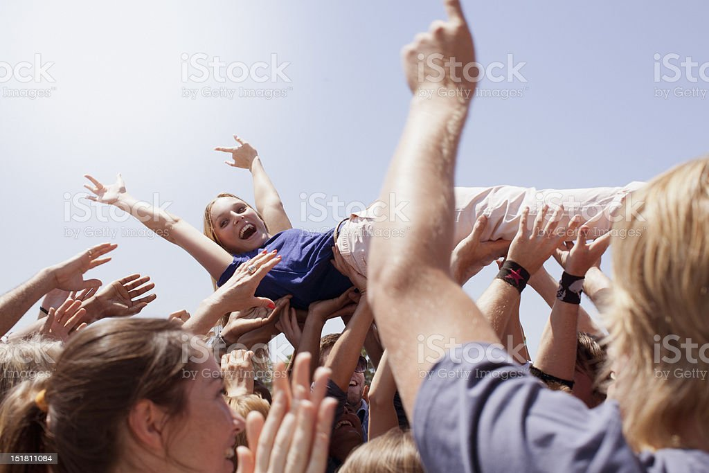 Enthusiastic woman crowd surfing stock photo