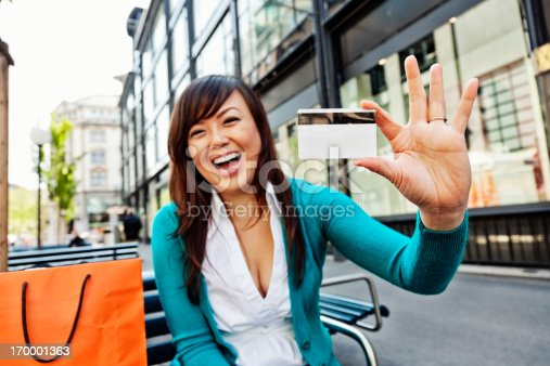 Photo of an attractive young Asian woman wearing a blue sweater, holding a blank credit card (or gift card). Primary focus on card and hand in foreground.