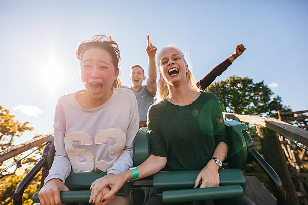 enthusiastic young friends riding amusement park ride - fahrgeschäft stock-fotos und bilder