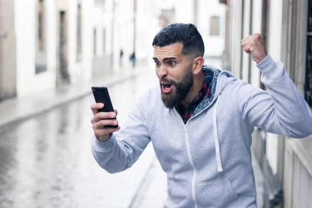 Enthusiastic young man looking at cellphone stock photo