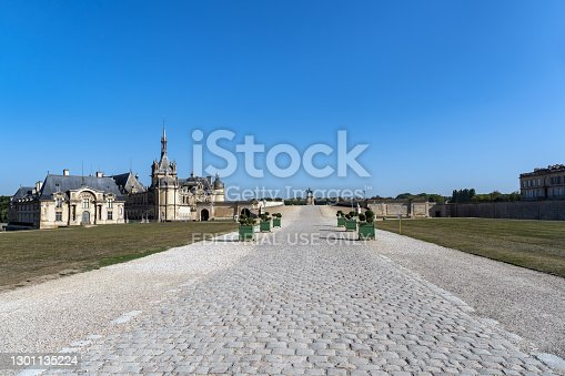 istock Entrance cobbled path to Chateau de Chantilly - France 1301135224