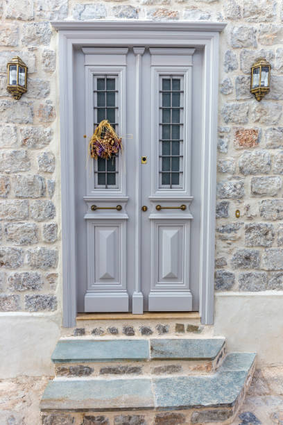 Entrance door with steps. Narrow traditional white street in the town of Hydra, Hydra island, Greece stock photo