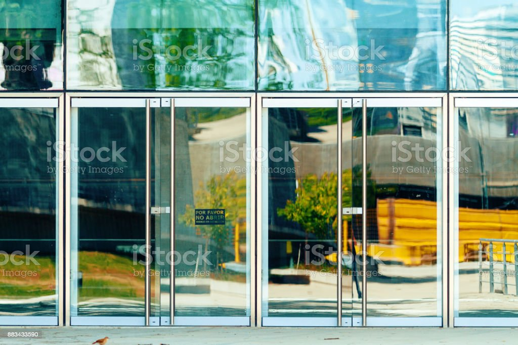 Entrance doors to an office building are a sign in Spanish of 'Please do not open' stock photo